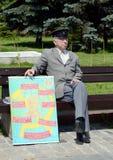 Ein unbekannter älterer Mann mit einem kommunistischen Plakat auf dem Poklonnaya-Hügel von Moskau Stockbilder