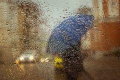 Ein undeutliches Schattenbild mit Regenschirm Lizenzfreie Stockbilder