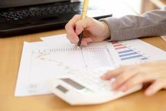 Ein Unternehmensberater arbeiten, um Unternehmensdaten vom Diagramm zu analysieren Lizenzfreie Stockbilder