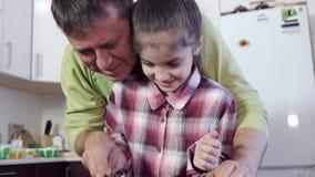 Ein Vater in der Küche unterrichtet seine Tochter, Gemüse mit einem Messer zu schneiden stock video footage