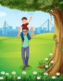 Ein Vater, der seinen Sohn nahe dem Baum über den Gebäuden trägt Stockfotos