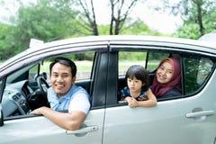 Ein Vater, eine Mutter und eine Tochter, die heraus von den offenen Fenstern schaut stockbild