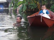Ein Vater nimmt seinen Sohn zur Sicherheit in einer überschwemmten Straße von Pathum Thani, Thailand, im Oktober 2011 lizenzfreies stockbild