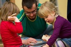 Vater, der Spielzeugblöcke mit Kindern spielt Lizenzfreies Stockbild