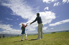 Ein Vater und seine junge Tochter, die einen Drachen fliegen Lizenzfreie Stockbilder
