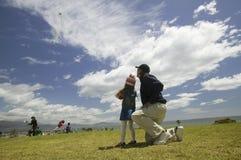 Ein Vater und seine junge Tochter, die einen Drachen fliegen Stockfotografie