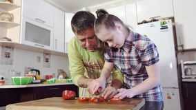 Ein Vater unterrichtet seine Tochter mit Down-Syndrom, wie man Gemüse schneidet stock footage