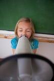 Ein verärgertes Schulmädchen, das durch ein Megaphon schreit Stockbild