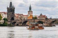Ein Vergnügensschiff auf dem Hintergrund Charles Bridges in Prag, Tschechische Republik lizenzfreie stockbilder