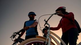 Ein verheiratetes Paar auf Fahrrädern im Hintergrund des aufgehende Sonne gehen auf eine Fahrradfahrt stock video