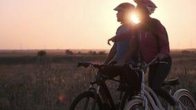 Ein verheiratetes Paar besprechen den Weg auf Fahrrädern gegen das aufgehende Sonne stock video