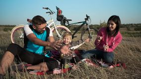 Ein verheiratetes Paar mit einem Kind auf dem Hintergrund ihrer Fahrräder Seifenblasen und Spaß stock video footage