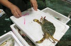 Ein Verkäufer, der den Preis auf einem Kasten mit einer frischen Krabbe markiert stockfotografie