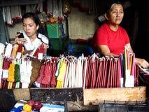 Ein Verkäufer neben der berühmten Antipolo-Kirche verkauft eine große Vielfalt gefärbt Kerzen Lizenzfreie Stockbilder