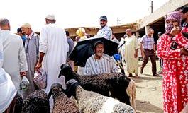 Ein Verkäufer von Schafen schützt sich vor der Sonne mit einem Regenschirm im souk der Stadt von Rissani in Marokko Lizenzfreie Stockfotos