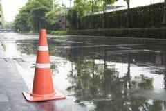 Ein Verkehrskegel auf der Straße in der Regenzeit und -reflexion Lizenzfreies Stockbild