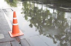 Ein Verkehrskegel auf der Straße in der Regenzeit und -reflexion Stockfotos