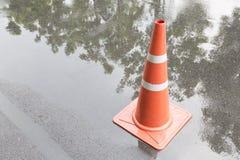 Ein Verkehrskegel auf der Straße in der Regenzeit und -reflexion Lizenzfreie Stockfotografie