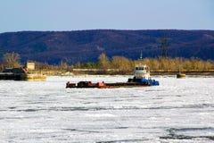 Ein Versandlastkahn steht mitten in einem eisigen Fluss lizenzfreies stockfoto