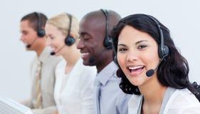 Ein verschiedenes Geschäftsteam, das auf Kopfhörer spricht
