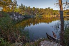 Ein versenktes Boot auf dem Ufer eines schönen Steinbruchs mit Trinkwasser Hoher Stein ukraine Lizenzfreies Stockbild