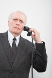 Ein verwirrter Geschäftsmann unter Verwendung eines Telefons Lizenzfreies Stockbild
