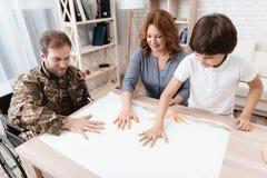 Ein Veteran in der Militäruniform in einem Rollstuhl verbringt Zeit mit seiner Familie Die Familie zeichnet zusammen Lizenzfreie Stockbilder
