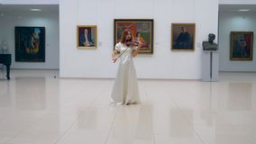 Ein Violinist führt in einem Museumsraum allein durch und steht in einer Mitte stock video