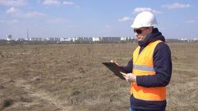 Ein Vorarbeiter ein Erbauer markiert Daten bezüglich eines leeren Feldes, um einen, Neubau, ein Wohngebiet, Industrie, Kopie zu e stock video