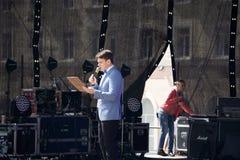 Ein Vorführer mit der Hand herauf das Geben von Darstellung, während Publikums-Leute in Konferenz Hall Auditorium aufpassen Blurr lizenzfreies stockfoto