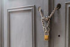 Ein Vorhängeschloß, das Ketten in einer Tür/in einem Tor hält lizenzfreies stockfoto