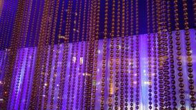 Ein Vorhang von den kleinen Metallperlen, die vor einem reflektierenden purpurroten und blauen Hintergrund hängen stockfotos