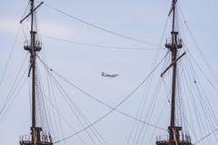Ein Vueling Airlines Flugzeug über Genua zwischen zwei Masten des Schiffs lizenzfreie stockfotografie
