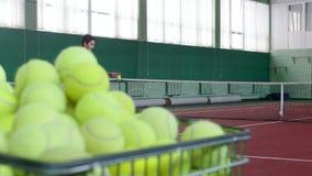 Ein Wagen gefüllt mit Tennisbällen Zwei junge Männer, die Tennis auf Tennisplatz auf dem Hintergrund spielen stock video