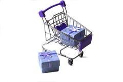 Ein Wagen von einem Supermarkt mit Geschenkboxen auf einem weißen Hintergrund Fahrwerkbeine und Frauenbeutel auf wei?em Hintergru stockfotografie