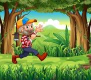 Ein Wald mit einem lächelnden Holzfäller, der eine Axt hält Lizenzfreies Stockbild