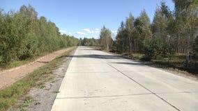 Ein Waldweg vorbereitet für Fahrzeugverkehr Betonstraße im Wald auf den neuen Fahrbahnmarkierungen der Betonstraße Straße konkret stock video footage