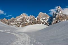 Ein Wanderer auf einem Weg auf dem Schnee, der das blasse von Bergen Sans Martino, Dolomit, Italien vorangeht Stockfoto