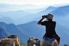 Ein Wanderer, der den Horizont sitzt und überwacht Lizenzfreie Stockfotos