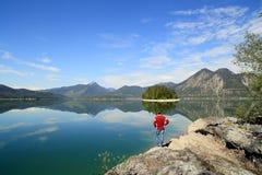 Ein Wanderer schaut zum schönen See lizenzfreie stockfotos