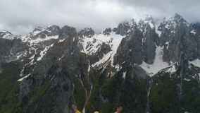 Ein Wanderer steht auf einen Berg und Blicke an den Schnee-mit einer Kappe bedeckten Bergen und hebt seine Hände in der Sieggeste stock video footage
