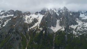 Ein Wanderer steht auf einen Berg und Blicke an den Schnee-mit einer Kappe bedeckten Bergen und hebt seine Hände in der Sieggeste stock video
