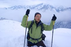 Ein Wanderermann, der in Winterberge geht lizenzfreies stockbild