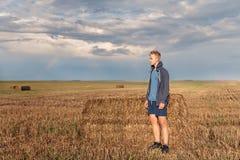 Ein wandernder Kerl in einem Hoodie in einer Haube betrachtet durchdacht einem Weizenfeld mit einem Hintergrund der untergehenden stockfotografie