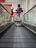 Ein Warenkorb auf Einkaufslaufkatzenrolltreppe füllte mit Waren und Babys lizenzfreies stockfoto