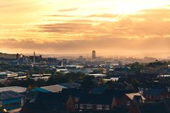 Ein warmer orange Sonnenuntergang hinter Wolken über Sheffield, South Yorkshire, Großbritannien stockfotos