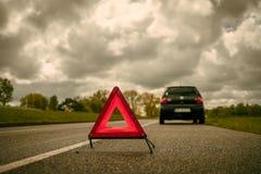 Ein Warndreieck vor einem Auto mit einem Zusammenbruch auf einem Seitenstreifen stockfotografie