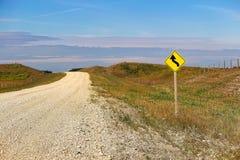 Ein Warnzeichen der Kurve voran neben einer Landstraße Stockbilder