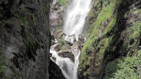 Ein Wasserfall auf einem Felsen mit Gras stock video