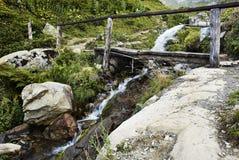 Ein Wasserfall in den Bergen und in einer Holzbrücke Lizenzfreies Stockfoto